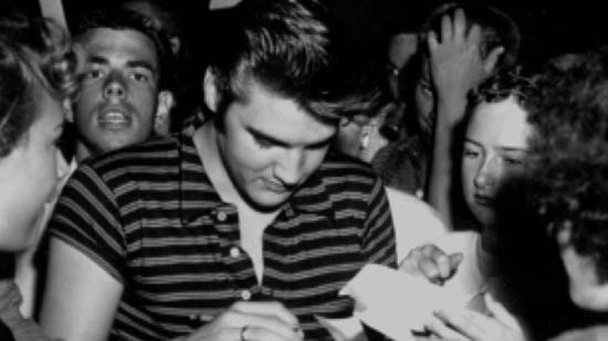 Elvis Presley fashion icon wearing a T-shirt - signing an autograph with loads of fans around him