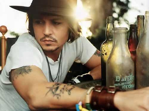 johnny depp  wearing leather bracelets showing his tattoos