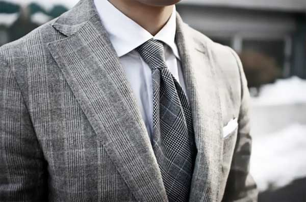 Checkered style grey tie matches the chequered grey suit